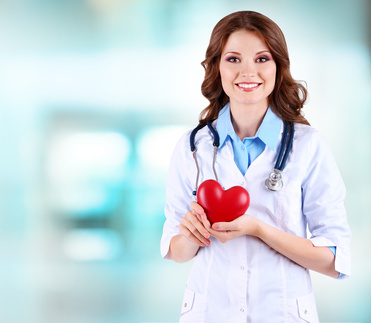Young beautiful doctor holding heart on hospital background